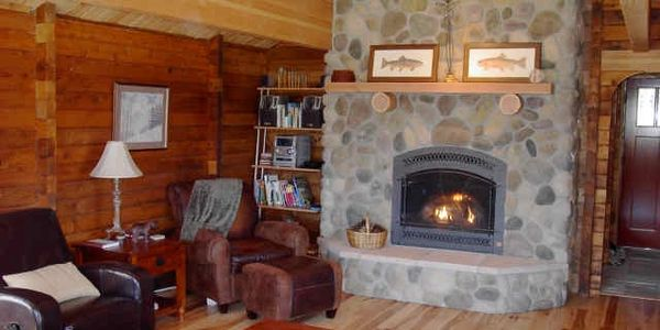 Cozy living room with river rock fireplace at Big Ponderosa vacation rental