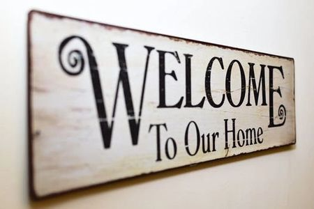 A sign is on a wall and it says Welcome to Our Home