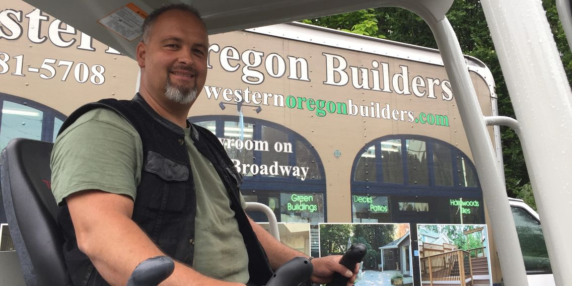 Alex, owner of Western Oregon Builders, in the excavator outside of a company van