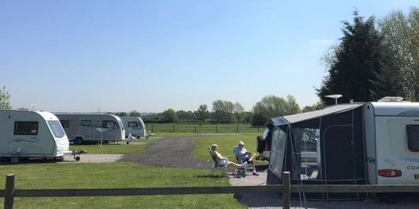 Caravans at Skybarn Farm CL with visitors sat outside in the sunshine