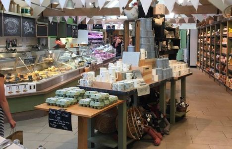 Inside  farm shop with counters and shelves full of items for sale and a deli counter