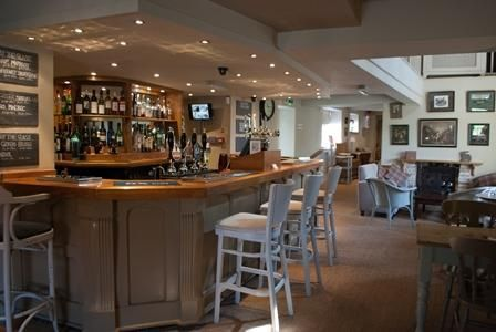 The bar at the Hare and Hounds, Fulbeck with bar stools and tables and chairs for diners to sit at