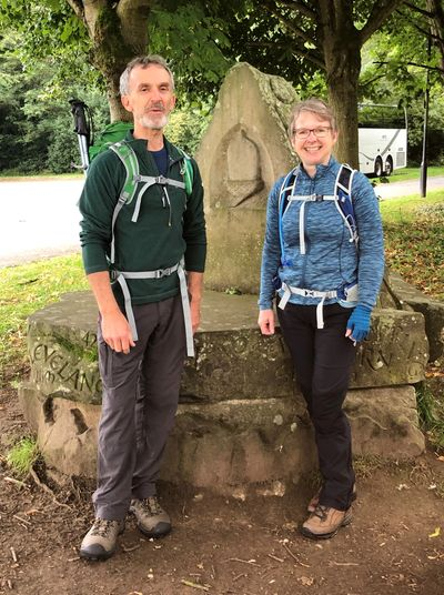 A lady and man posing for a photograph at the start of the Cleveland Way in Helmsley