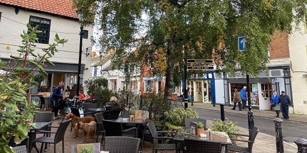A street in Southwell town centre with people sitting outside at tables and chairs eating