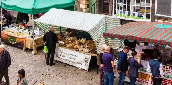 Farmers' market stalls on a cobbled street in Lincoln with people shopping and queueing to buy items