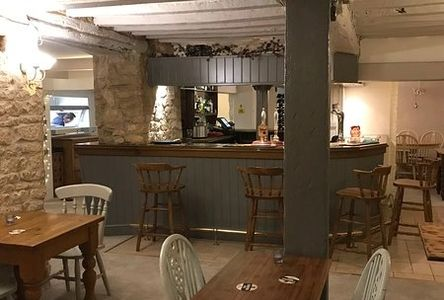 Inside view of the White Hart pub with bar stools and tables with painted chairs