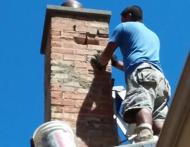 this is a chimney being tuck pointed and replacing old bricks