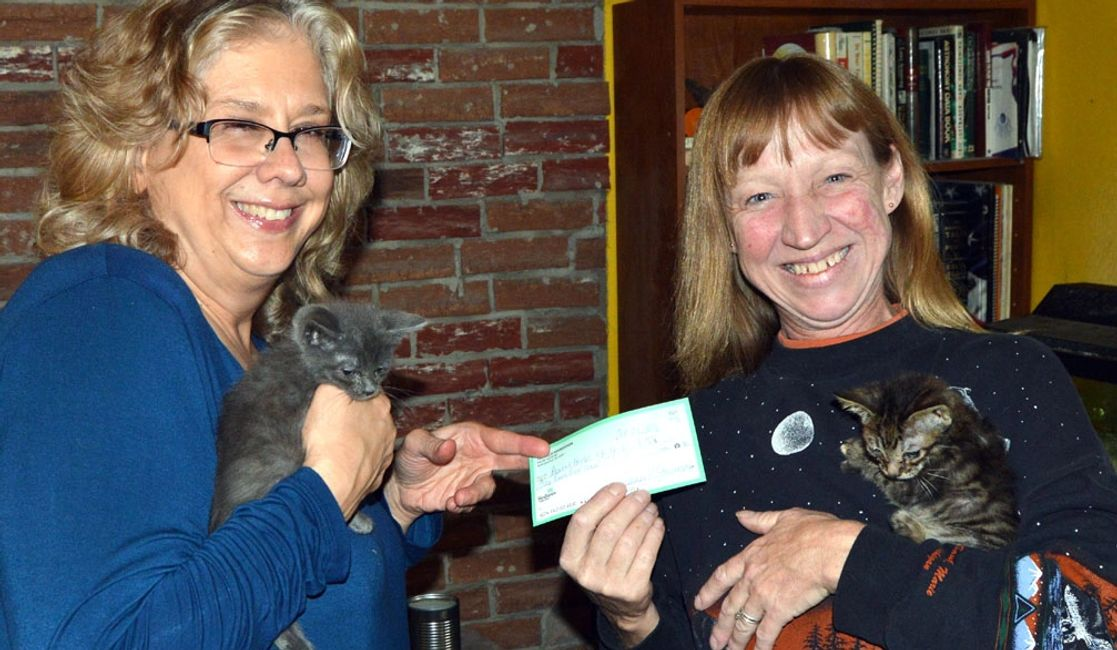 Jeanne Starmack, left, chairwoman of the Allie Foundation, gives a check for $100 to Denise Herbe of