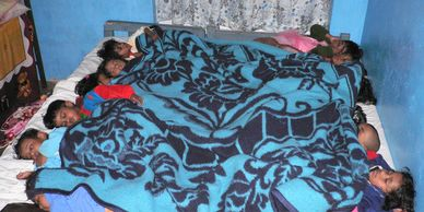Orphans napping all in one bed at the Kodaikanal orphanage