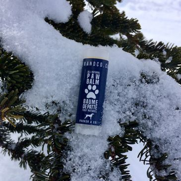 Parker & Co. Fast Healing Paw Balm on a tree with snow.