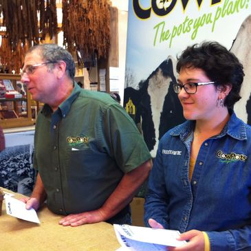 Farmer and daughter promote and discuss CowPots at event.
