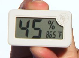 A humidity gauge being held between an index finger and a thumb
