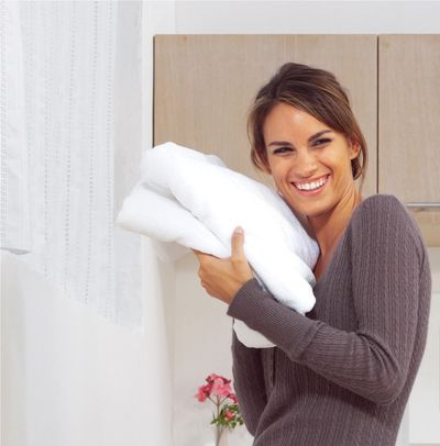 Woman smiling holding freshly washed towels.