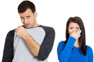 Male holding the collar corner of his T-shirt to his nose with a disgusted expression, and a female
