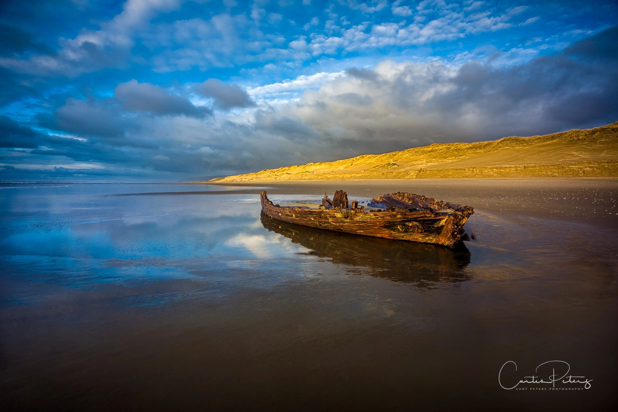 Ship wreck in Florence, Oregon along the sand dunes. Clouds, water, reflections, sand dunes.