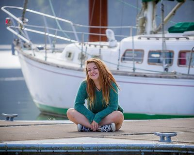 High school senior portrait of a girl sitting at the docks with a sail boat in the background