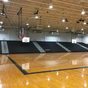 Bleachers and basketball backstop in a gymnasium/athletic facility.