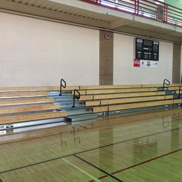 Wooden bleachers in school gymnasium/athletic facility.