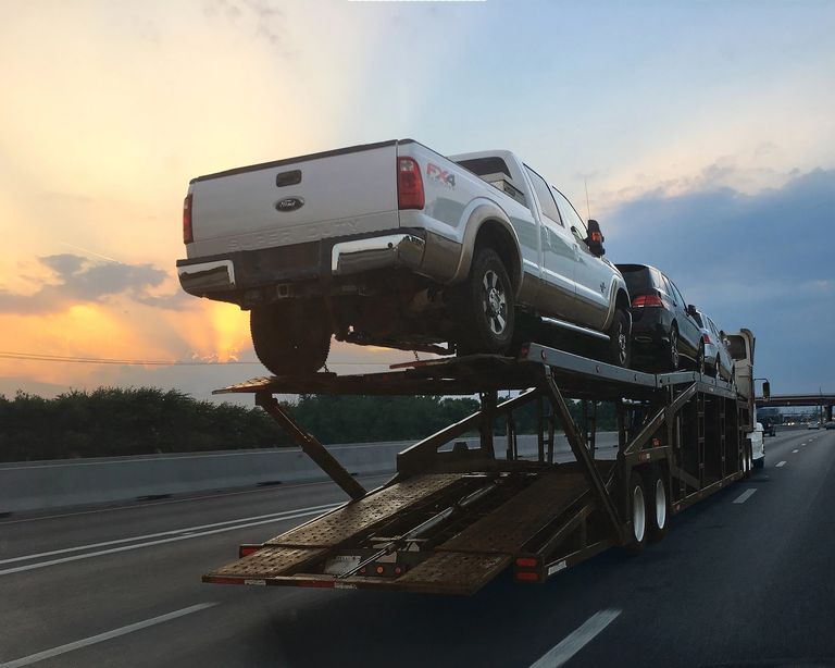 Car carrier with pickup truck on the back and sunset in the background.  Auto shipping car hauler