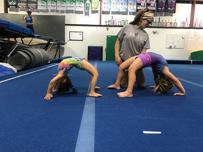 Girls doing a bridge with coach spotting