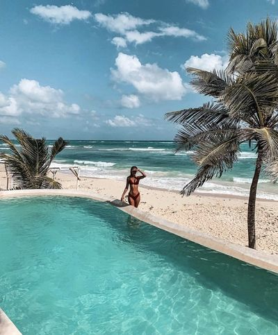 Woman standing by pool in front of sandy beach and Caribbean sea