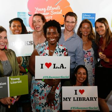 Trish at a L.A. Public Library event, standing with a group before the step and repeat, holding a si