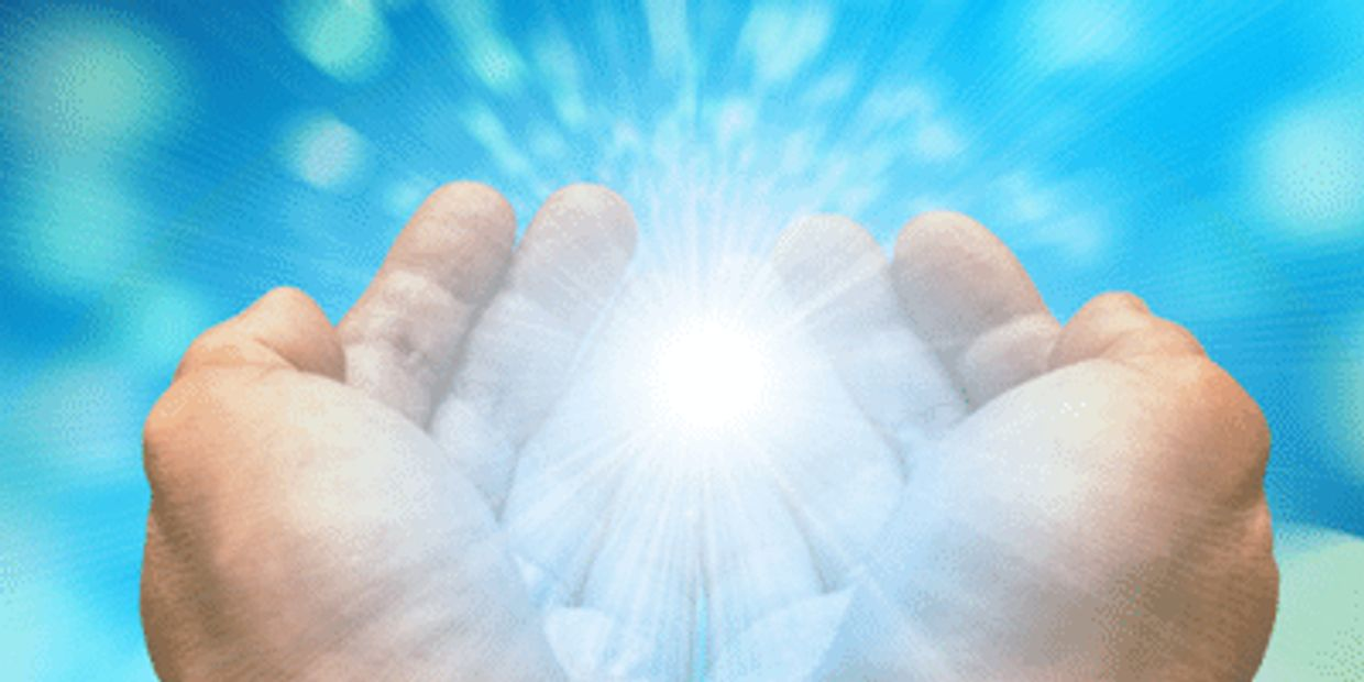 Hands holding white light with blue background.