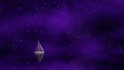 Lone sailboat on a dark, starry night.