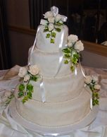 4 tier wedding fondant wedding cake with handmade sugar ivory roses and edible pearls.