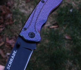 Schrade knife with small flakes of mica that change the knives color dependent on angle