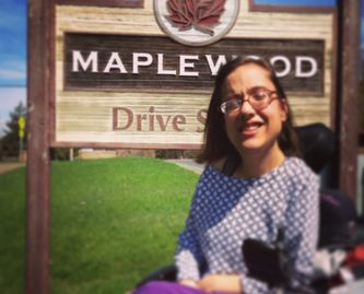 nikki sitting in her wheelchair, in front of maplewood sign