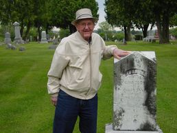 Russell Grinolds with the gravemarker of his great-grandfather, John M. Grinolds in Mauston, WI