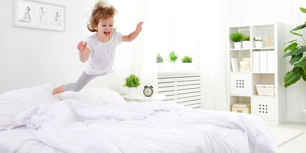 Little girl in white outfit jumping on bed with clean white sheets