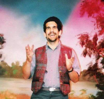 Barry in a blue shirt and maroon patterned vest telling a story in front of a background featuring t