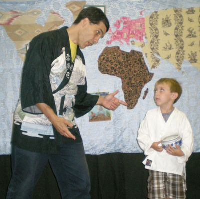 Barry in a Chinese jacket, in front of a fabric world map, talking to a boy volunteer helping to ena