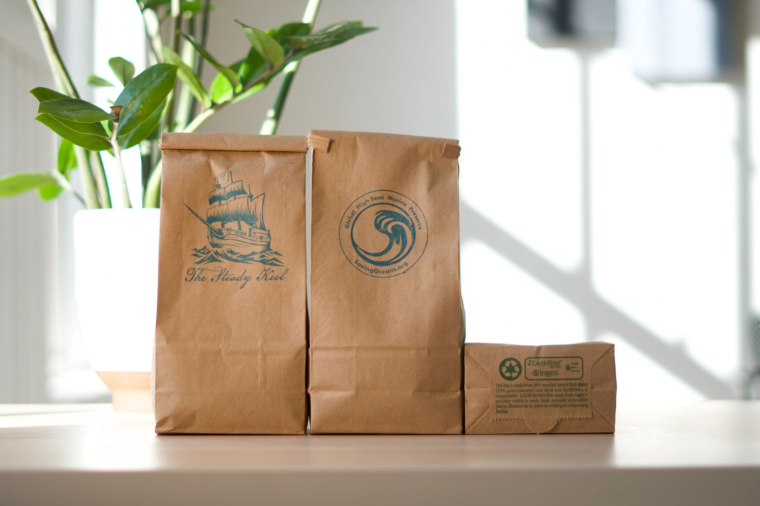 Three bags of The Steady Keel coffee sit atop a table in a well lit room.