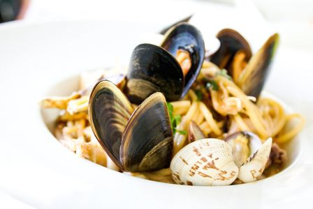 A clam seafood pasta dish in a white bowl.