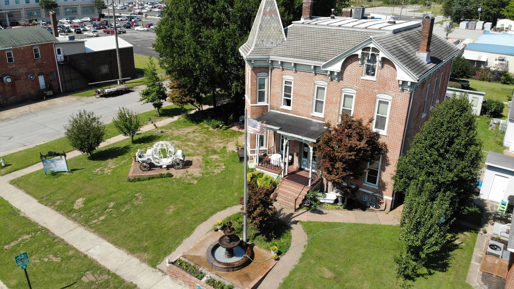 Aerial view of three story, brick mansion with an eight foot tall fountain in the front garden.