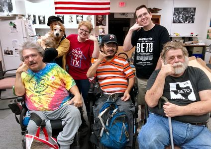 Photo of phone bankers at ADAPT of Texas office, with Rue, the service dog