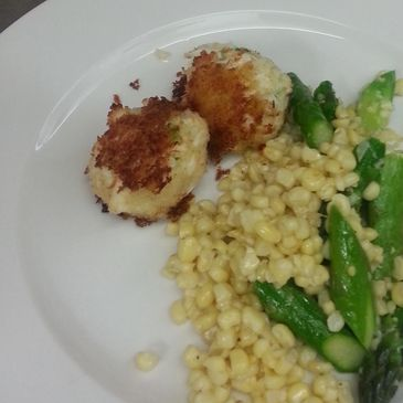 Crab cakes served with Corn-Asparagus saute.