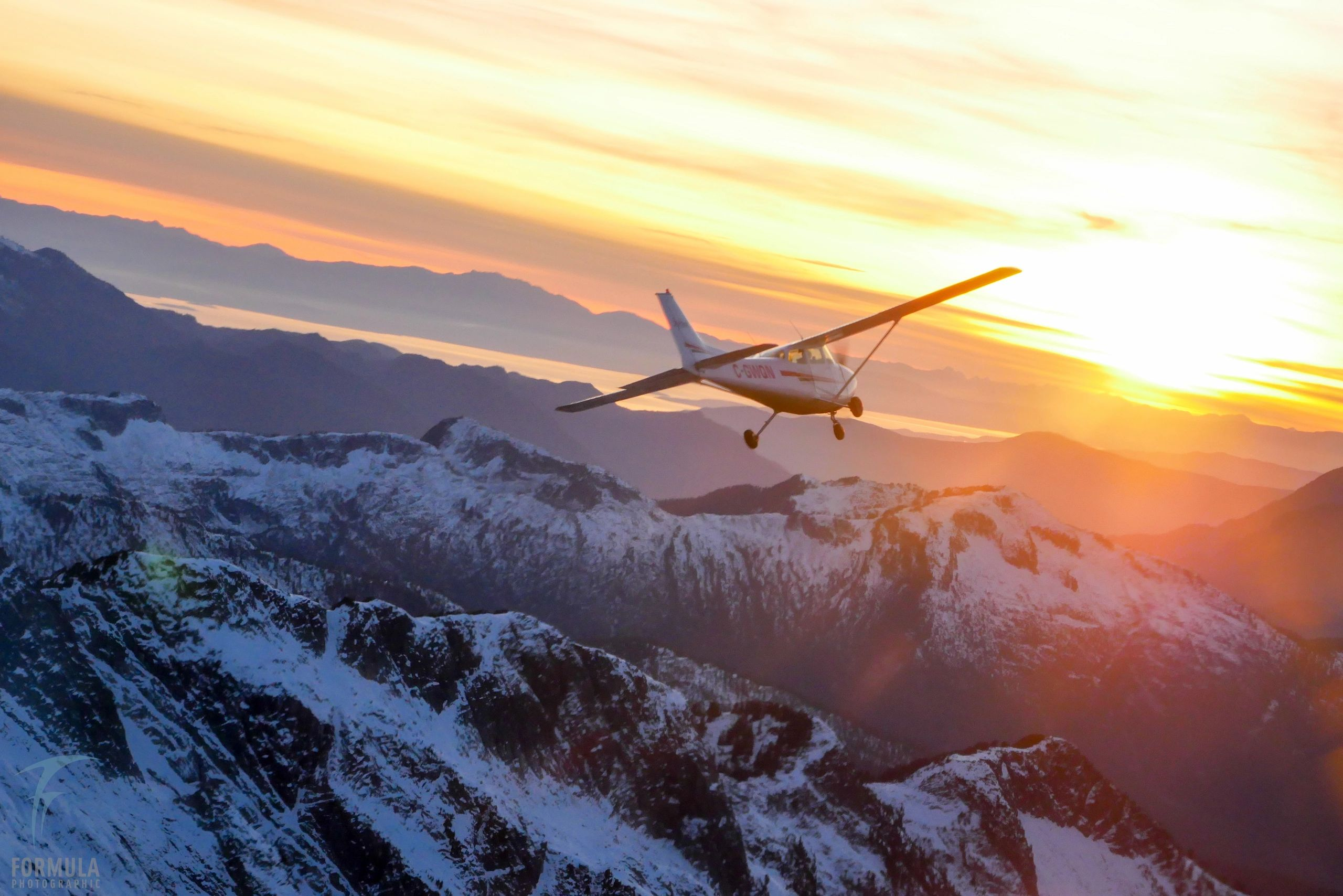 Cessna flies into the sunset over mountains of British Columbia.
