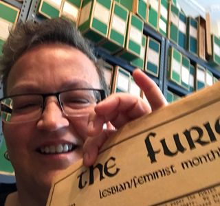 Jackie Rhodes smiles broadly while holding a copy of THE FURIES newspaper up to the camera.