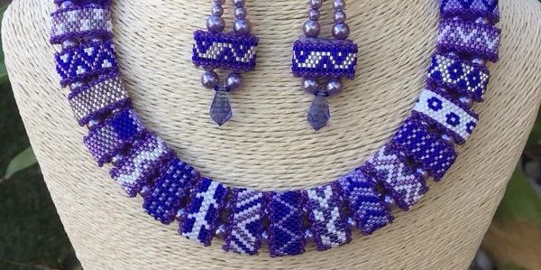 Custom seed bead purple necklace and earrings on a necklace stand