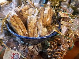 Antique bowl filled with chocolate dipped Biscotti & surrounded by chocolate dipped Pretzels.
