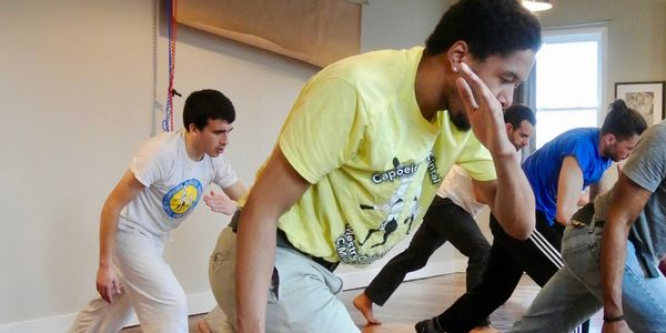 Students practice the basic movement of capoeira, the ginga, in a class