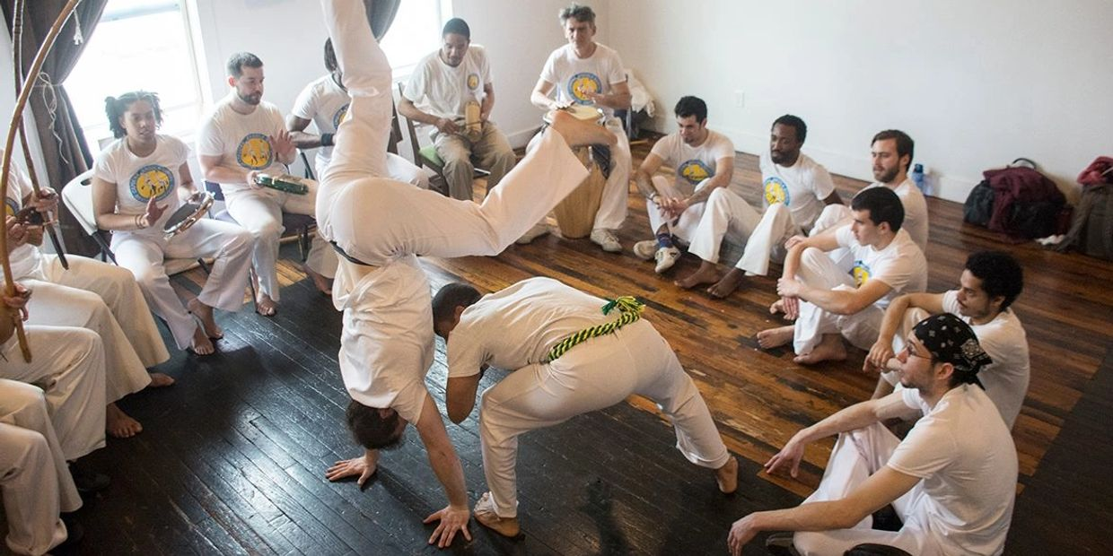 Two people play a game of capoeira inside the roda (circle)