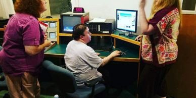 A client working at a community access TV station and learning how to use editing software.