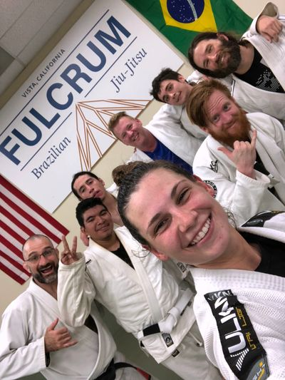 Our awesome team of male and female Brazilian jiu-jitsu practitioners smiling for the camera.