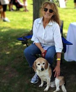 Founder of White Whiskers Senior Dog Sanctuary, Polla Milliga, sitting with dog, Henry.