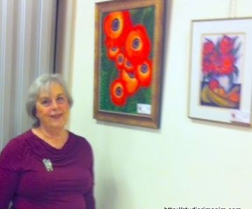Leah Laker with her paintings at an exhibition held at AACI in Jerusalem.